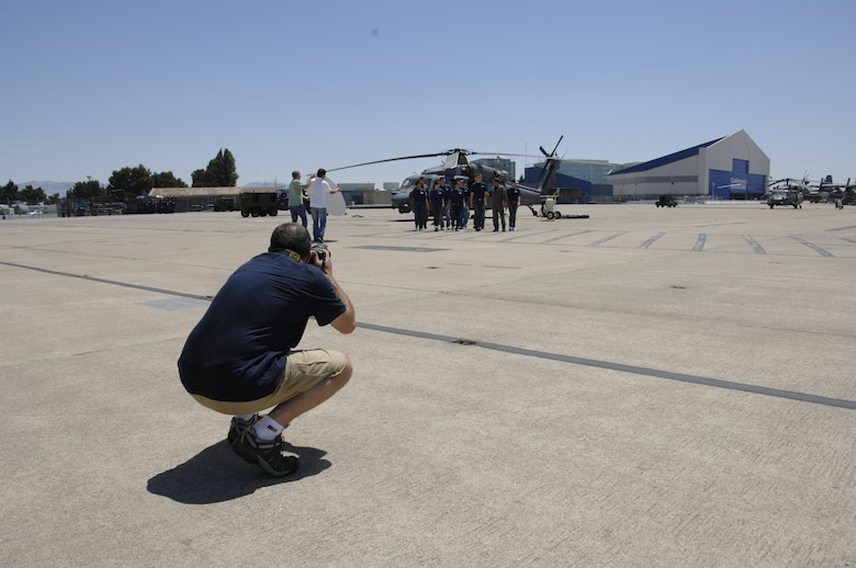 Master Sgt. Rob Trubia, superintendent of the Air National Guard Advertising and Marketing Creative Branch, takes photos of the 129th Rescue Wing student flight during a photo shoot for the redesign of GoANG.com at Moffett Federal Airfield, Calif., Aug. 1, 2009. (Air National Guard photo by Tech. Sgt. Ray Aquino)