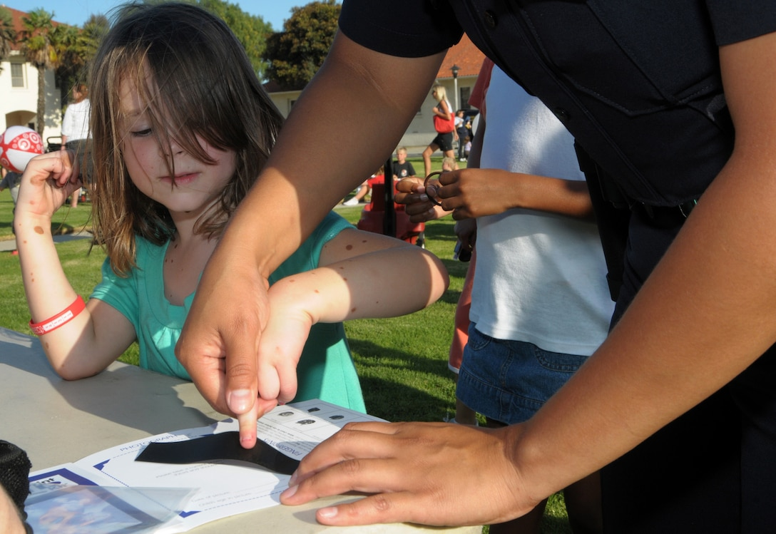 Family Member Mackenzie Fox gets finger printed at the National Night Out event at Fort MacArthur, Aug. 4. Families gathered to enjoy food, meet Mc Gruff the Crime Dog and local fire department reps, and other activities in observance of the event where neighborhoods across the country take back the night from crime.  (Photo by Joe Juarez)