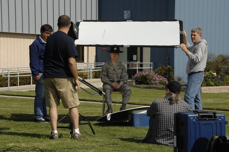 Members from the Air National Guard Advertising and Marketing team set up video equipment for an interview with Master Sgt. Alan Munro, a former military training instructor and a member of the 129th Medical Group, during a video and photo shoot for the redesign of GoANG.com at Moffett Federal Airfield, Calif., Aug. 1, 2009.  (Air National Guard photo by Senior Airman Shane Burke)