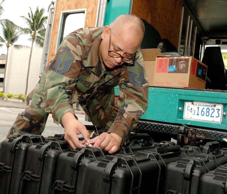 Master Sgt. Robert Tancayo, 624th Civil Engineer Squadron, inspects weapon cases before distributing them to reservists in his squadron July 31, 2009. Fifty-four reservists from the squadron were mobilized for six months and sent to Bagram Airfield, Afghanistan, to support the U.S. Army. (U.S. Air Force photo/Mark Bates)