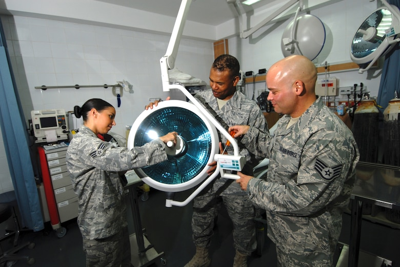Left to right, Senior Airman Candice Cimball, 379th Expeditionary Medical Group medical logistics technician, Master Sgt. Lancelott Harris, 379 EMDG medical logistics NCOIC, and Staff Sgt. William Travis, 379 EMDG biomedical equipment technician, install new surgical operating lights in the clinic's emergency room, here, Aug. 5. Airman Cimball hails from Seattle and is deployed from Keesler Air Force Base, Miss. Sergeant Harris is a native of Lauderhill, Fla., and is assigned here as permanent party. Sergeant Travis is a native of Gulf Port, Miss., and deployed from Keesler AFB. All servicemembers are supporting Operations Iraqi and Enduring Freedom.  (U.S. Air Force Photo/Tech. Sgt. Jason W. Edwards)