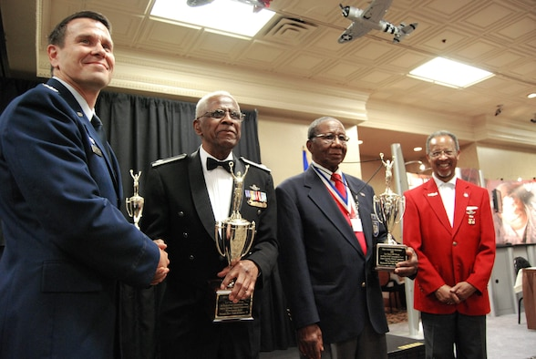 """Col. John Montgomery (left) pauses for a photo with retired Lt. Col. James Harvey, retired Chief Master Sgt. Buford Johnson and Tuskegee Airmen Inc. President Russell Davis during the 60th anniversary recognition ceremony of the """"Gunsmoke"""" competition for sharp shooters Aug. 6 at the Palace Station Hotel in Las Vegas. The event occurred during the 38th annual TAI National Convention Aug. 6 through 9. Colonel Montgomery is the Range Wing commander at Nellis Air Force Base, Nev. (U.S. Air Force photo/Tech. Sgt. Amaani Lyle)"""