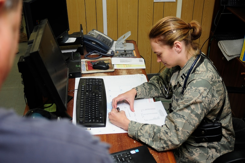 """ALI BASE, Iraq -- U.S. Air Force Capt. Christine Smetana, Family Medicine Doctor, writes a perscription for a patient at the """"Doc in the Box"""" here, July 4, 2009. (U.S. Air Force photo by Airman 1st Class Tony R. Ritter)"""
