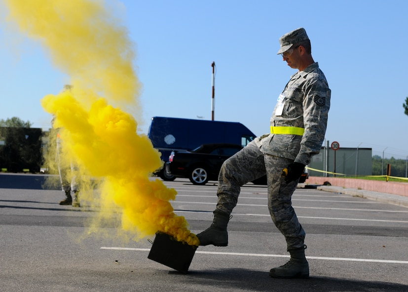 SPANGDAHLEM AIR BASE, Germany -- Tech Sgt. Jeffrey Morman, 52nd Maintenance Group exercise evaluation team, releases yellow smoke to simulate an indirect fire attack in the parking lot of the 81st Fighter Squadron Aug. 4. The smoke was used as a visual indicator of an explosion for nearby players in the 52 FW's Phase II exercise here. This Phase II is the first of five total exercises to prepare the 52nd Fighter Wing for a NATO Tactical Evaluation in June 2010. (U.S. Air Force photo/Airman 1st Class Nathanael Callon)