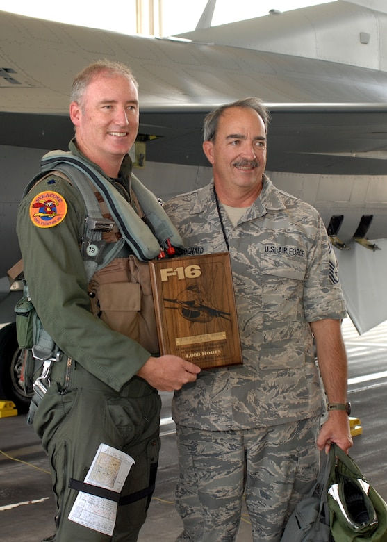 Lt. Col. D. Scott Brenton a pilot assigned to the 174th Fighter Wing, Hancock Field, Syracuse, NY posses with Senior Master Sgt. Christopher McDonald a crew chief commemorating Lt. Col. Brenton's achievement of flying more then 4,000 hours inside the cockpit of the F-16 Fighting Falcon.