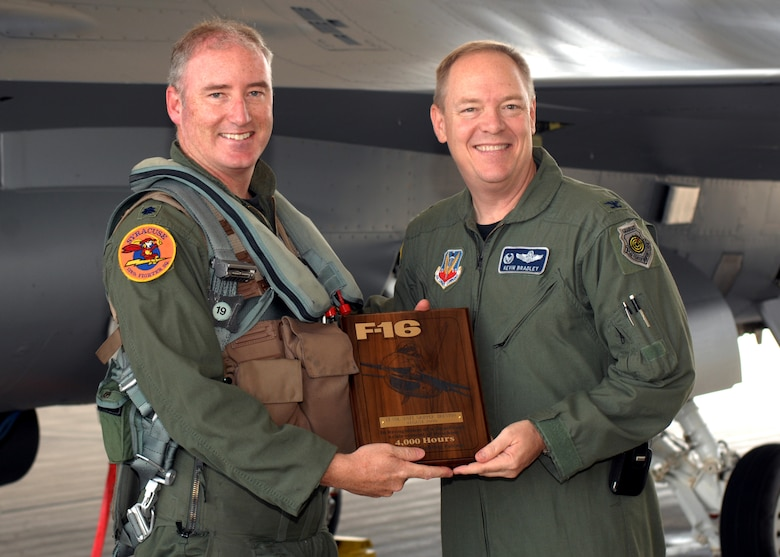 Col. Kevin W. Bradley, 174th Fighter Wing Commander, Syracuse, NY, presents a plaque to Lt. Col. D. Scott Brenton commemorating his achievement of flying more then 4,000 hours inside the cockpit of the F-16 Fighting Falcon.