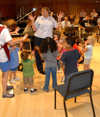 Master Sgt. Cheryl Sizer engages with children enrolled at the Child Development Center on Peterson Air Force Base, Colo., for fun with live music at the U.S. Air Force Academy Band's facility on Peterson AFB. Among the children in attendance was Sergeant Sizer?s daughter, Sophia, to her immediate left. (U.S. Air Force photo/Larry Hulst)
