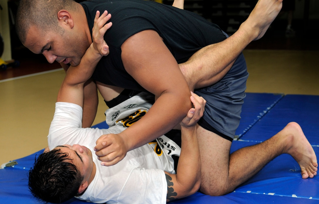 Staff Sgt. Michael Limiac, a 39th Medical Support Squadron medical information systems technician, keeps Staff Sgt. Roberto Cruz, a 39th Comptroller Squadron budget analyst, in his guard during a mixed martial arts training session Friday, Aug. 7, 2009 in the Fitness Center at Incirlik Air Base, Turkey.  Sergeant Limiac coordinates the workout sessions three times per week.  Participants of all skill levels attend the workouts and train to build on their knowledge of the sport.   More than 20 Airmen have attended the workouts since implementation.  (U.S. Air Force photo/Staff Sgt. Raymond Hoy)