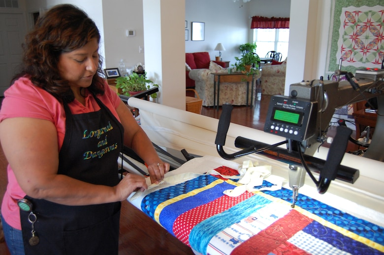 "Irene Hafer of Dover, Delaware, checks the edge on a Quilts of Valor quilt in her home studio June 24, 2009. Her apron reads ""Longarmed and Dangerous,"" a reference to the longarm machine she uses to stitch together the three layers of a quilt. (U.S. Air Force photo/Tech. Sgt. Benjamin Matwey)"