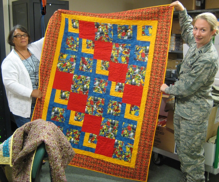 Angie Carr and Capt. Sandra Bannan display a Quilt of Valor June 12, 2009 at the Air Force Mortuary Affairs Operations Center located at Dover A.F.B., Delaware. Quilts of Valor have been awarded to several hundred workers at the center since late 2006. (U.S. Air Force photo/Tech. Sgt. Benjamin Matwey)
