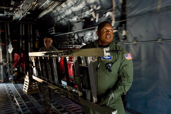 "Master Sgt. L.T. ""Peppy"" Smith, a flight examiner for the 167th Aeromedical Evacuation Squadron, and Airmen Joseph Robert carry a ladder through a C-130 aircraft during an egress training session at the 167th Airlift Wing, West Virginia Air National Guard. The 167th AW secured the C-130, which was headed to the ""bone yard"" at Davis-Monthan Air Force Base, and will convert it to a training simulator for the base. (U.S. Air Force photo by Master Sgt Emily Beightol-Deyerle)"