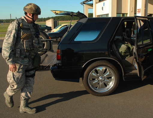 SPANGDAHLEM AIR BASE, Germany -- Staff Sgt. Joseph Null, 52nd Security Forces Squadron, inspects a vehicle at the front gate Aug. 4 during a base-wide exercise in preparation for a NATO Tactical Evaluation scheduled for 2010. For elevated security conditions, it is protocol for security forces to inspect every vehicle that comes through the gate. (U.S. Air Force photo /Airman 1st Class Nick Wilson)