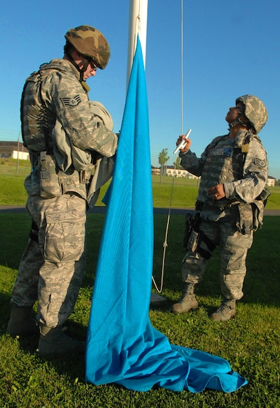 SPANGDAHLEM AIR BASE, Germany -- Staff Sgt. Corina Manzanares and Staff Sgt. Joseph Null, 52nd Security Forces Squadron, prepare to raise a U.S. Air Forces in Europe communication flag at the front gate Aug. 4 during a base-wide exercise in preparation of a NATO Tactical Evaluation scheduled for 2010. USAFE headquarters periodically selects colored flags to be raised as part of a force-protection measure to evaluate base response times. (U.S. Air Force photo/ Airman 1st Class Nick Wilson)