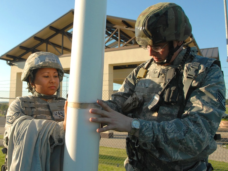 SPANGDAHLEM AIR BASE, Germany -- Staff Sgt. Corina Manzanares and Staff Sgt. Joseph Null, 52nd Security Forces Squadron, tighten the rope of a U.S. Air Forces in Europe communication flag at the front gate Aug. 4 during a base wide exercise in preparation of a NATO Tactical Evaluation scheduled for 2010. USAFE headquarters periodically orders Airmen to raise a colored flag as part of a force protection measure to evaluate base response times. (U.S. Air Force photo/ Airman 1st Class Nick Wilson)