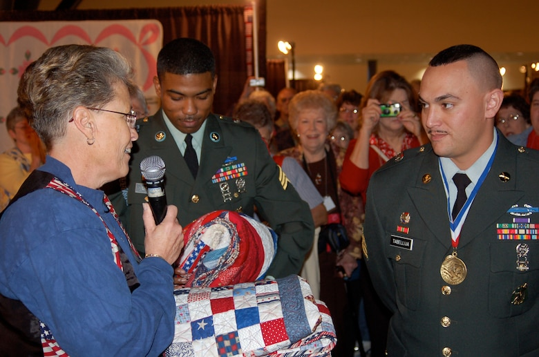 Gail Belmont, operations officer for the Quilts of Valor Foundation, awards quilts to U.S. Army Sgt. Crooks and Sgt. Tabellija during the opening of the Houston International Quilt Festival, Nov. 1, 2007, in Houston, Texas. (Photo courtesy of Catherine C. Roberts, Quilts of Valor Foundation)