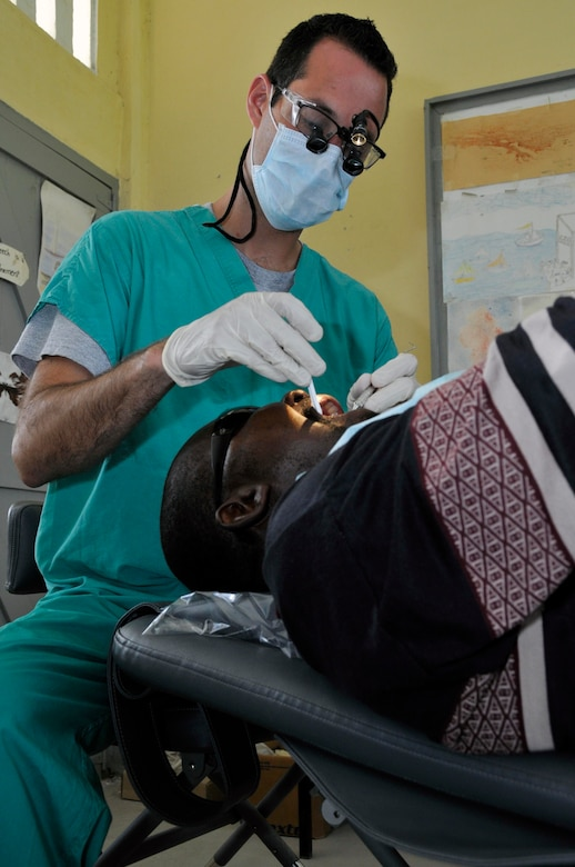 Capt. Theadore Jackson, Dentist from the 375th Dental Squadron, Scott AFB, Illinois, gives a Guyanese man a filling at the Diamond School Aug 10, 2009, in Diamond, Guyana. Providing free dental care is just one part of the New Horizons Guyana humanitarian mission. More than 650 service members are providing assistance during this mission by building medical clinics and schools and providing free medical, dental and optometry care.(U.S. Air Force photo by Airman 1st Class Perry Aston) (Released)