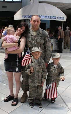Staff Sgt. Adam Moses of the 445th Security Forces Squadron waits in the baggage claim area at the Dayton International Airport, Ohio, Aug. 6, 2009. Joining him are his wife, Sheila, holding their daughter Rayvin, and their older son Dante and younger son Kain. Sergeant Moses was one of 12 reservists from Wright-Patterson Air Force Base, Ohio, to return home after six months at Kirkuk Regional Air Base, Iraq. (U.S. Air Force photo/Stacy Vaughn)