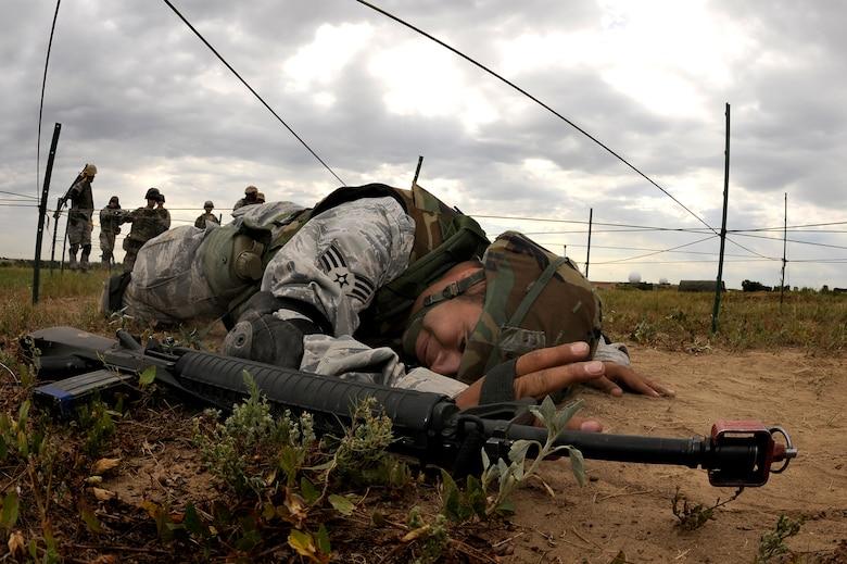 Senior Airman Raymond Gonzales, 460th Civil Engineering Squadron, low crawls under rope during DREST. (U.S. Air Force photo by Senior Airman Steve Czyz)