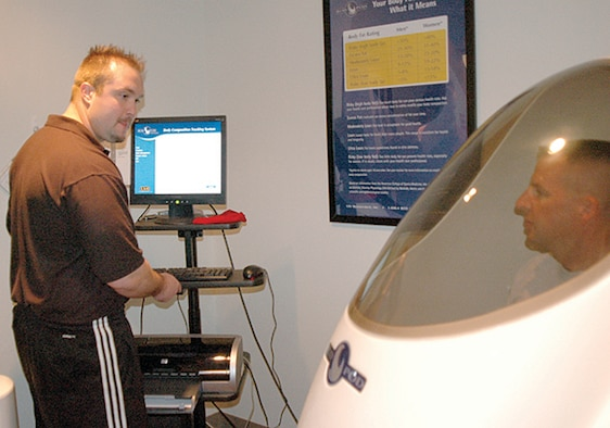 Col. Patrick Higby, 75th Air Base Wing commander, takes a body composition test in the Bod Pod at the Health and Wellness Center as Ryan Burns, 75th Aerospace Medicine Squadron exercise physiologist, records the results.