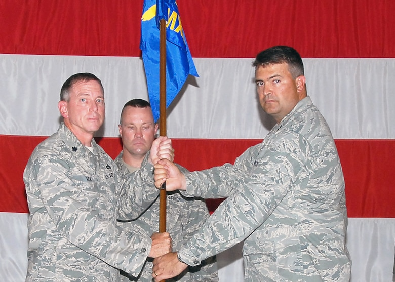 Capt. Kirby Findley accepts the 131st Maintenance Squadron flag from Lt. Col. Mark Beck, 131st Maintenance Group commander, during the 131st BW Assumption of Commands ceremony held Aug. 8, at the Army National Guard Armory, Whiteman Air Force Base, Mo. (U.S. Air Force Photo by Master Sgt. Mary-Dale Amison)