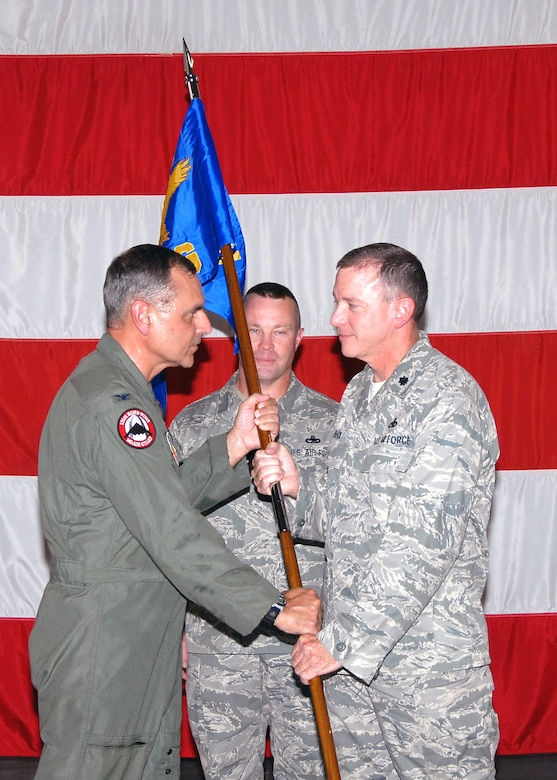 Lt. Col. Mark Beck accepts the 131st Maintenance Group flag from Col. Robert L. Leeker, 131st BW commander, during the 131st BW Assumption of Commands ceremony held Aug. 8, at the Army National Guard Armory, Whiteman Air Force Base, Mo. (U.S. Air Force Photo by Master Sgt. Mary-Dale Amison)
