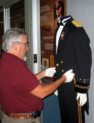 "Paul Martin adjusts the tail coat on General Henry ""Hap"" Arnold's formal evening dress uniform in the recently completed Arnold Hall exhibit at the U.S. Air Force Academy in Colorado Springs, Colo., Aug. 11, 2009. Mr. Martin is a museum specialist and the curator of collections for the Academy. (U.S. Air Force photo/Ken Carter)"