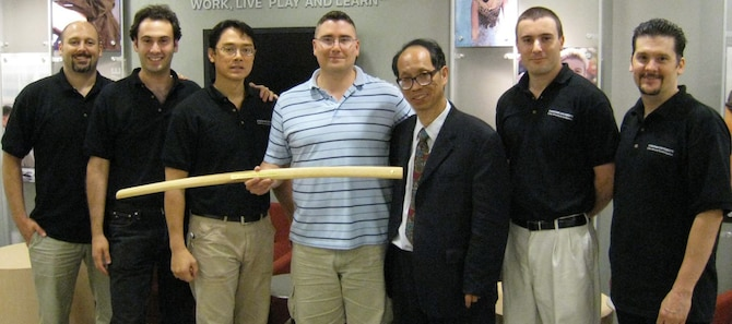 "Capt. Michael Henson (center) displays a bokken he received after a cyberspace-based ""capture the flag"" event held by the New York City chapter of Infragard July 21-22. Captain Henson, an assistant professor of computer science at the U.S. Air Force Academy in Colorado Springs, Colo., started the Cadet Cyber Warfare Club to train cadets on network attack and defense skills. He was a member of an aggressor team during the event and appears here with members of the opposing Blue Team. (U.S. Air Force photo)"