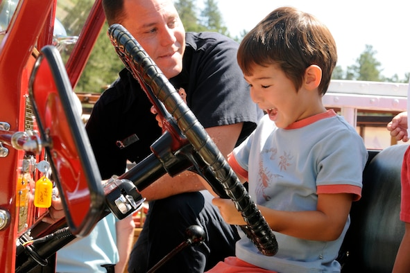 Two-year-old Sebastian Smits plays with the steering wheel of a fire truck under the supervision of firefighter Shaun Glidden from Fort Carson, Colo., during a U.S. Air Force Academy Fire Department Open House held Aug. 8. (U.S. Air Force photo/J. Rachel Spencer)