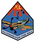 "The sky blue patch is an odd diamond shape edged in black. Along the bottom edge, against a gray background, are the black words ""CLOSING FOR THE KILL."" In the top corner, a red sun has four red sunbeams protruding outward. Inside the sun is the Roman numeral ""XL."" A camouflaged P-40 Warhawk with a tigershark mouth dominates. The aircraft fires six .50 caliber machine guns, and in the background a black enemy aircraft falls out of the sky, leaving a trail of black smoke.
