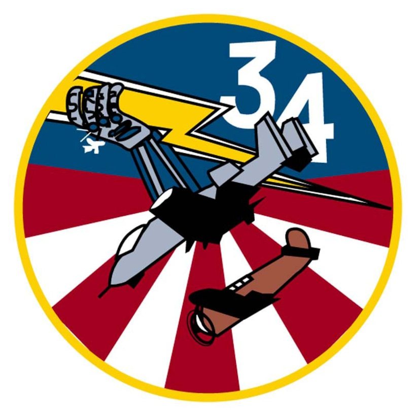 "The patch is a circle with a gold border. The top half of the background is blue with a white ""34"" in the upper tight. The lower half of the filed has alternating red and white stripes converging at the center of the patch. A gray A-10 Thunderbolt II with a P-47 Thunderbolt immediately below it dominates the center. A bolt of lightning, gold with a white border, extends from the upper left to the lower right. A gray and purple armored hand holds the bolt, and Polaris lies immediately below the hand.