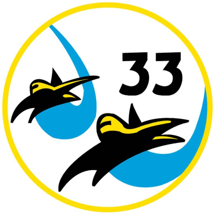 """The patch is a white circle outlined in gold. Two black falcons, diving in formation, leave blue contrails. The black numeral """"33"""" is located in the patch's upper right portion.The two spacecraft-like falcons represent the mascot of the Air Force Academy, the bird of prey noted for its speed, keen eyesight and fierce fighting spirit. They fly in formation to show the teamwork of the members of the cadet wing and the Air Force.This is the squadron's original patch."""