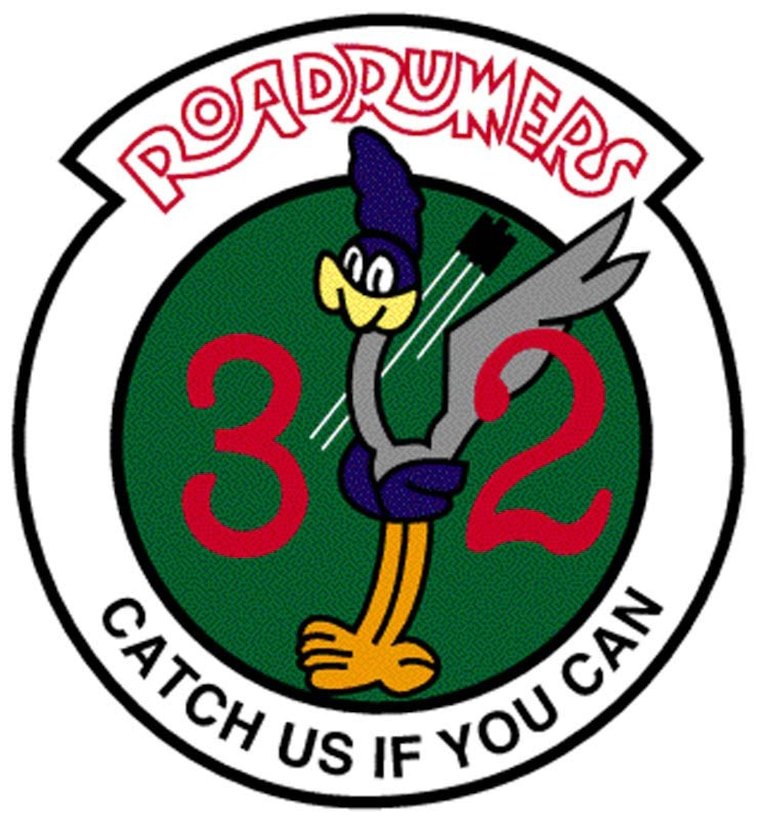 "The patch, bordered in dark green and white, is an emerald green with an aircraft and its contrails are in the center. The dark red inscription ""Roadrunners"" is at the top. The Roadrunners, a cartoon character, and the bright orange numeral ""32"" dominate the field. The squadron motto, ""Catch Us If You Can,"" is on the bottom of the patch.