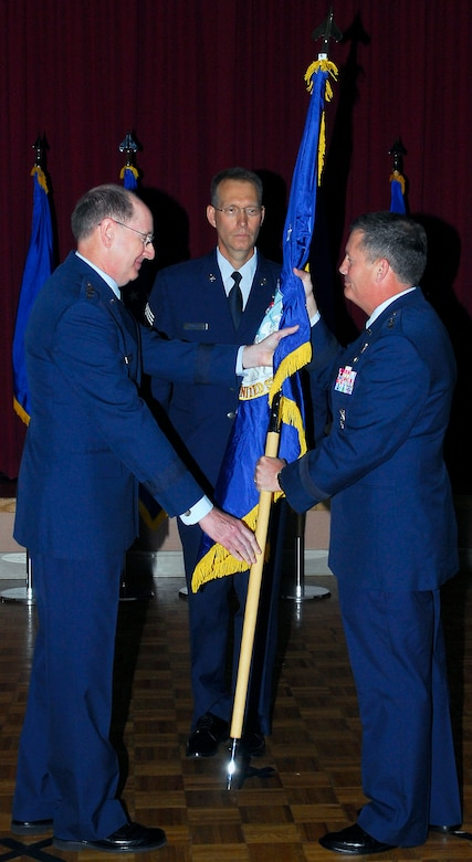 Gen. C. Robert Kehler, commander Air Force Space Command, passes the official flag to Maj. Gen. Richard E. Webber, making him the first commander of the 24 AF.  Chief Master Sgt. Todd Small, AFSPC command chief, looks on.  The 24th Air Force activation under Air Force Space Command is a major milestone in the combination of space and cyberspace operations within one command. General Kehler presided over the ceremony to activate the new numbered Air Force. (Courtesy photo)
