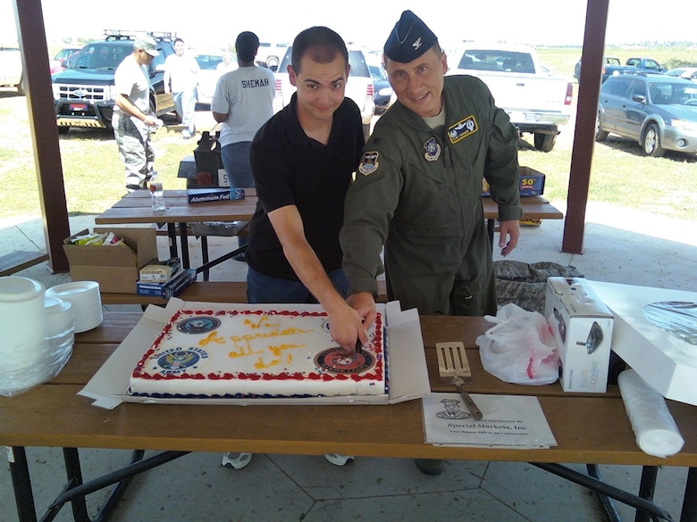 BUCKLEY AIR FORCE BASE, Colo. -- Col. Clint Crosier (right), 460th Space Wing commander, and Airman Matthew Mendez, 460th Space Communications Squadron, cut the cake at Junior Enlisted Appreciation Day picnic at Lake Williams Aug. 7. Team Buckley's 5/6 Association put on the event for the E-1 through E-4 Airmen, Soldiers, Sailors and Marines on Buckley, (U.S. Air Force photo)