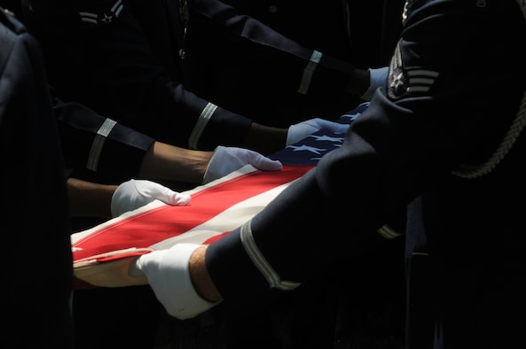 A United States Air Force Honor Guard body bearer team folds the U.S. flag during a full honors funeral ceremony at Arlington National Cemetery. Honor guard body bearers train constantly to maintain the precision they are known for. Their standards of flawlessness are set out of necessity to honor fallen Airmen. (U.S. Air Force photo by Senior Airman Sean Adams)