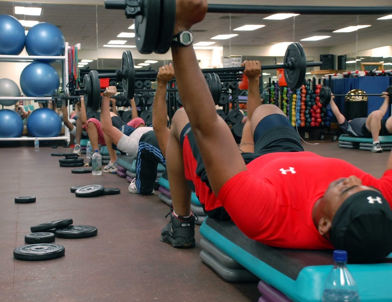 Master Sgt. Keith Vernon, 9th Force Support Squadron, bench presses his barbell Aug. 17 at the fitness center. Sergeant Vernon, along with other active-duty Airmen are training to be the only certified Body Pump instructors in the Air Force. (Photo by Sandy Healy)