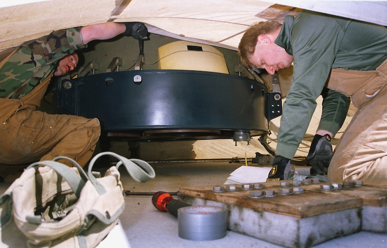 In the narrow space between the top of the launcher closure door and thrust nozzles of a suspended Minuteman III,  Staff Sgts. Jordan Hatch and Dean Phelan, 341st Maintenance Squadron technicians, remove tie-downs to lower the missile into launch facility Hotel-02 April 16, 2001, during the first booster replacement at Malmstrom.  (U.S. Air Force photo/John Turner)