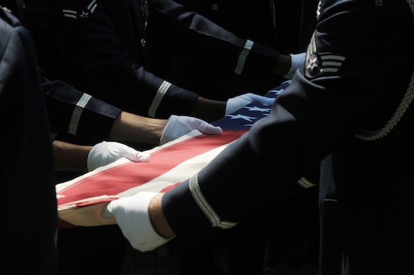 A United States Air Force Honor Guard body bearer team folds the U.S. flag during a full-honors funeral ceremony at Arlington National Cemetery. Honor Guard body bearers train constantly to maintain the precision they are known for. Their standards of flawlessness are set out of necessity to honor fallen Airmen. (U.S. Air Force photo/Senior Airman Sean Adams)