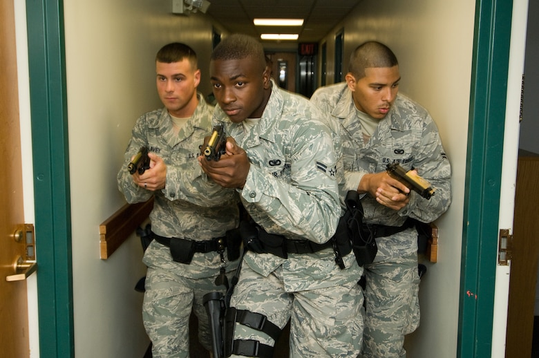 HANSCOM AIR FORCE BASE, Mass. - (From Left) Airman 1st Class Jeffrey Lavey, Airman 1st Class Nicholas Taylor, and Airman 1st Class Abraham Medina, with Staff Sgt. Christopher Darrow (not pictured, in rear), all with the 66th Security Forces Squadron, move along the corridors of the dormitories on Aug. 6 during a training session with the Massachusetts State Police Special Tactical Operations Team where they learned how to diffuse an active-shooter scenario. (U.S. Air Force photo by Rick Berry)
