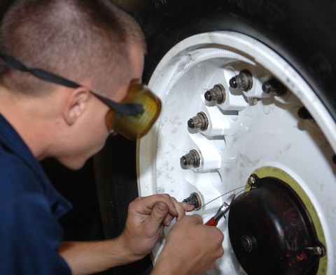 Senior Airman Brian Decker, 34th Maintenance Unit crew chief, attaches safety wire to a bolt on the B-1B Lancer's wheel here, August 19. The wire keeps the bolt from moving when the B-1 is in flight. (U.S. Air Force photo/ Airman 1st Class Jarad A. Denton)