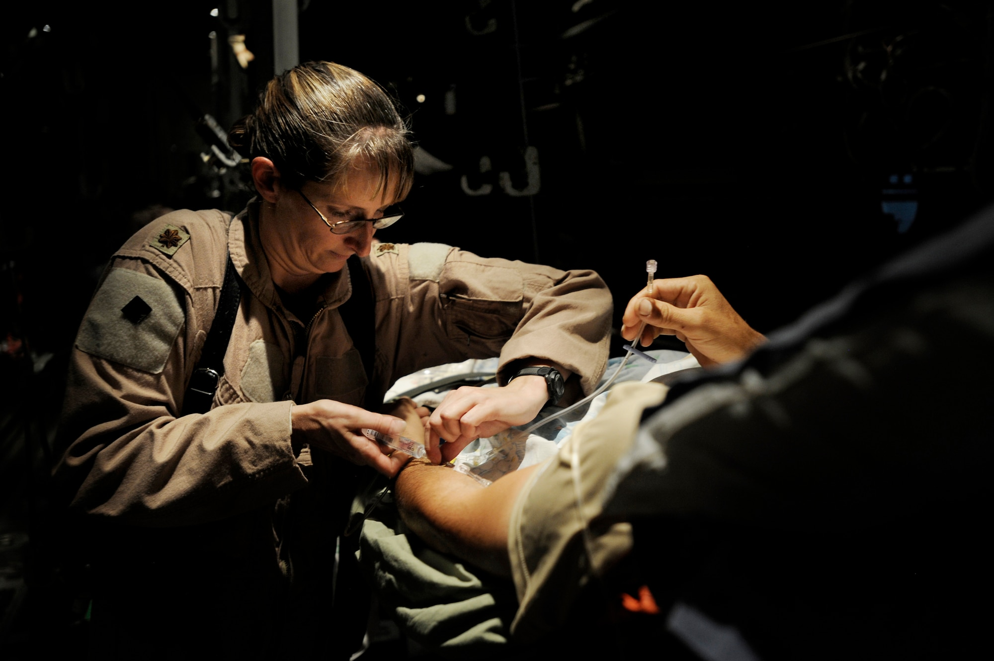Maj. Missy Steckler provides care to a patient during a flight to a location that can provide a higher level of medical care. Major Steckler is a flight nurse assigned to the 451st Expeditionary Aeromedical Evacuation Flight at Kandahar Airfield, Afghanistan. (U.S. Air Force photo/Staff Sgt. Shawn Weismiller)