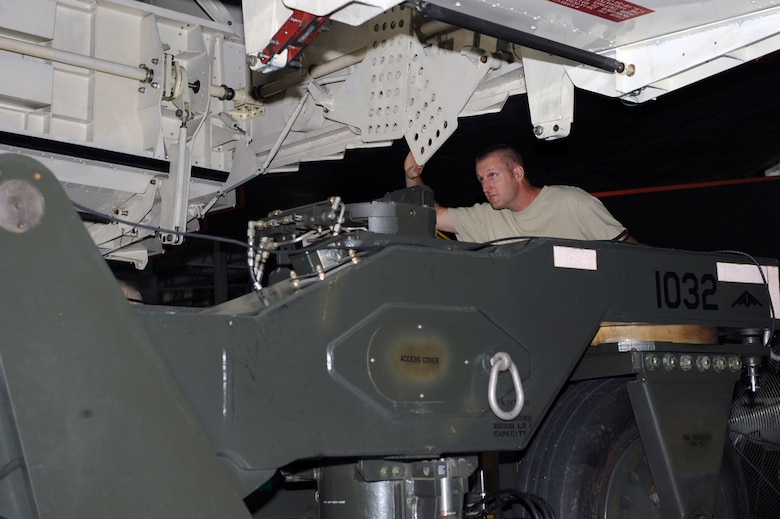 WHITEMAN AIR FORCE BASE, Mo. – Tech. Sgt. Ryan Graney, Loading Standardization Crew member, assists in guiding a weapons trailer under the Weapons Load Trainer Aug. 14. Loading and unloading the WLT, as well as an actual B-2, requires a four-man team of certified weapons system loaders. (U.S. Air Force photo/Senior Airman Jason Huddleston)