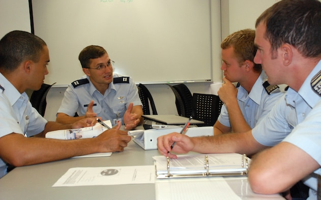 Capt. Luke Sauter reviews ins and outs of rocketry to Cadets 1st Class Aaron Price, Wayne Black and Nolan Brock. Captain Sauter was recently selected as the Air Force nominee for the 60th-annual Arhut S. Flemming Award for Applied Science, Engineering and Mathematics. He is an astronautics course instructor with the U.S. Air Force Academy's Department of Astronautics. (U.S. Air Force photo/Ann Patton)