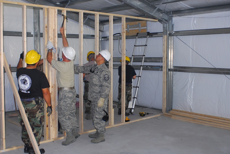 Members of the 149th Civil Engineer Squadron erect an interior wall for an office in the Expeditionary Medical Support (EMEDS) building, on the grounds of the Military Central Hospital in Yerevan, Armenia. The Texas Air National Guard civil engineers deployed from San Antonio, Texas, to Yerevan to work on security cooperation initiatives and humanitarian assistance projects during the first two weeks of August 2009. The EMEDS building will accommodate medical equipment, supplies, tents and personnel to facilitate Armenian response to natural disasters and wartime contingencies. (Texas Military Forces photo by Tech. Sgt. Rene Castillo)