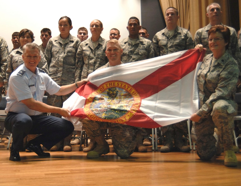 Florida Air National Guard Commander Brig. Gen. Joseph Balskus (left) and 290th JCSS Commander Lt. Col. Loretta Lombard (right) present a State of Florida flag to Maj. Rick Basting (center) and the deploying members of the 290th JCSS during a ceremony at MacDill Air Force Base, Aug. 16, 2009. Photo by Tech. Sgt. Thomas Kielbasa