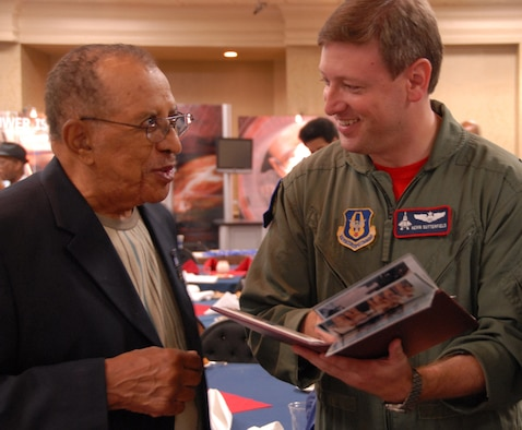 Retired Lt. Col. James Warren, one of the original Tuskegee Airmen, swaps flying stories with Maj. Kevin Sutterfield of the 302nd Fighter Squadron during the Tuskegee Airmen's 38th Annual National Convention Aug. 6, 2009. Colonel Warren is the honorary commander of the Air Force Reserve Command's 477th Fighter Group, Elmendorf Air Force Base, Alaska, and a former member of the 477th Bombardment Group. The 477th BG activated during World War II as part of the historic Tuskegee Airmen. The group was reactivated in 2007 when the 477th Fighter Group became the Air Force Reserve Command's first F-22 Raptor unit. (U.S. Air Force photo/Maj. Cary McPartlin)