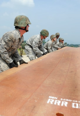 Airmen from the 51st Civil Engineer Squadron unfold a fiberglass mat on the simulated runway before it is put into place at Jungwon Air Base, Republic of Korea Aug 19. The 30-foot long, 54-foot wide foot mats are used to quickly repair runway damage, and can be connected to cover a large area. The mats are being moved as part of a joint combined rapid runway repair training exercise with Airmen from the Republic of Korea Air Force's 19th Tactical Fighter Wing and 91st Air Civil Engineer Group.  The 51st CES is assigned to Osan Air Base, Republic of Korea. (U.S. Air Force photo/Senior Airmen Stephenie Wade)