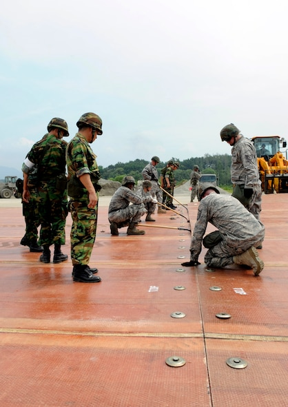 Airmen from the 51st Civil Engineer Squadron use shovels to lift a folded fiberglass mat as a 10,000-pound forklift adjusts the mat on a simulated runway at Jungwon Air Base, Republic of Korea, Aug 19.  The mats are being moved as part of a joint combined rapid runway repair training exercise with Airmen from the Republic of Korea Air Force's 19th Tactical Fighter Wing and 91st Air Civil Engineer Group.  The 51st CES is assigned to Osan Air Base, Republic of Korea. (U.S. Air Force photo/Senior Airmen Stephenie Wade)