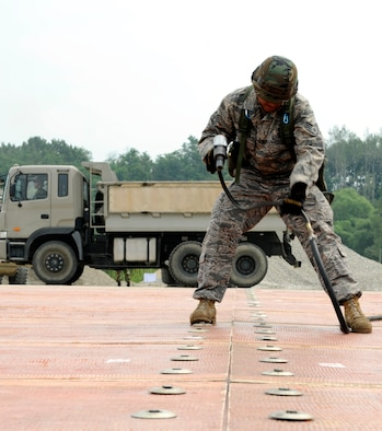 Staff Sgt. William Deguzman uses an air compressor to connect two folded fiberglass mats together on a simulated runway at Jungwon Air Base, Republic of Korea Aug 19. The 30-foot long, 54-foot wide foot mats are used to quickly repair runway damage, and can be connected to cover a large area. This process was part of a joint combined rapid runway repair training exercise with Airmen from the Republic of Korea Air Force's 19th Tactical Fighter Wing and 91st Air Civil Engineer Group.  Sergeant Deguzman is assigned to the 51st Civil Engineer Squadron, Osan Air Base, Republic of Korea. (U.S. Air Force photo/Senior Airmen Stephenie Wade)