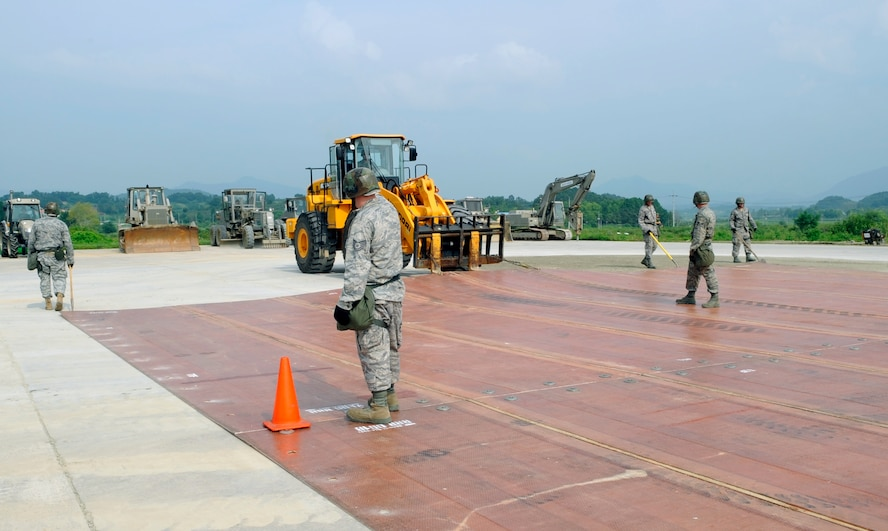 Airmen from the 51st Civil Engineer Squadron stand on a folded fiberglass mat as it is moved into place by a 10,000-pound forklift on a simulated runway at Jungwon Air Base, Republic of Korea, Aug. 19. The 30-foot long, 54-foot wide mats are used to quickly repair runway damage, and can be connected to cover a large area. The mats are being moved as part of a joint combined rapid runway repair training exercise with Airmen from the Republic of Korea Air Force's 19th Tactical Fighter Wing and 91st Air Civil Engineer Group.  The 51st CES is assigned to Osan Air Base, Republic of Korea. (U.S. Air Force photo/Senior Airmen Stephenie Wade)